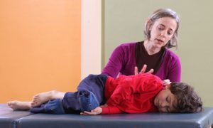 Janelle practicing Feldenkrais with Toddler on table